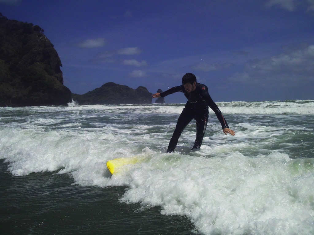Riding the surf at Piha Beach